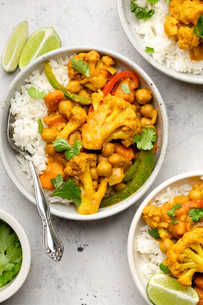 Vegan chickpea curry with cauliflower and veggies in a bowl with rice. It is garnished with cilantro. Next to it is more bowls of curry and some lime wedges.