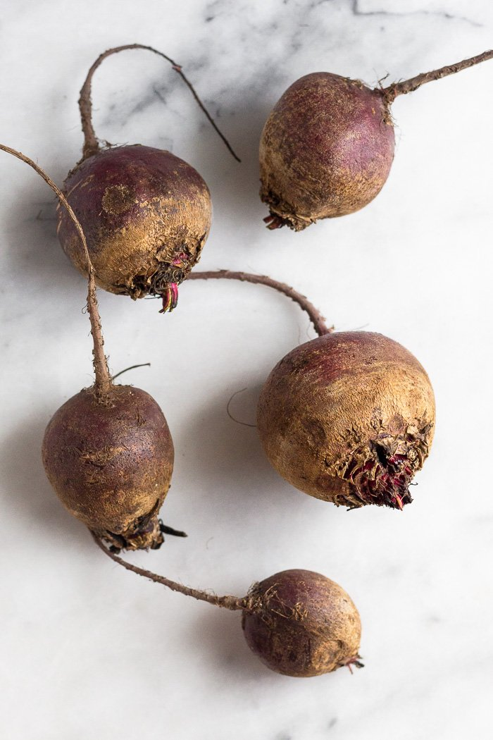 Five raw beets on a white countertop.