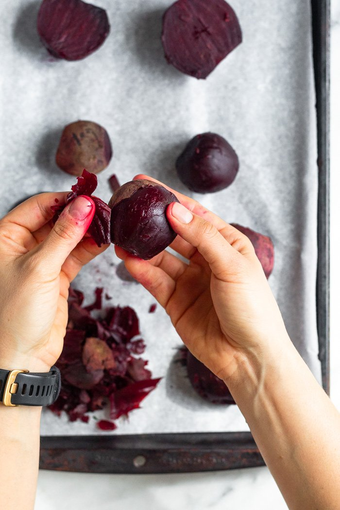 Overhead shot of two hands peeling cooked beets. Underneath of them is more beets on a baking sheet.