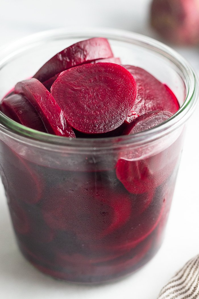 Easy pickled beets in a large jar with a kitchen towel next to them and some beets behind them.
