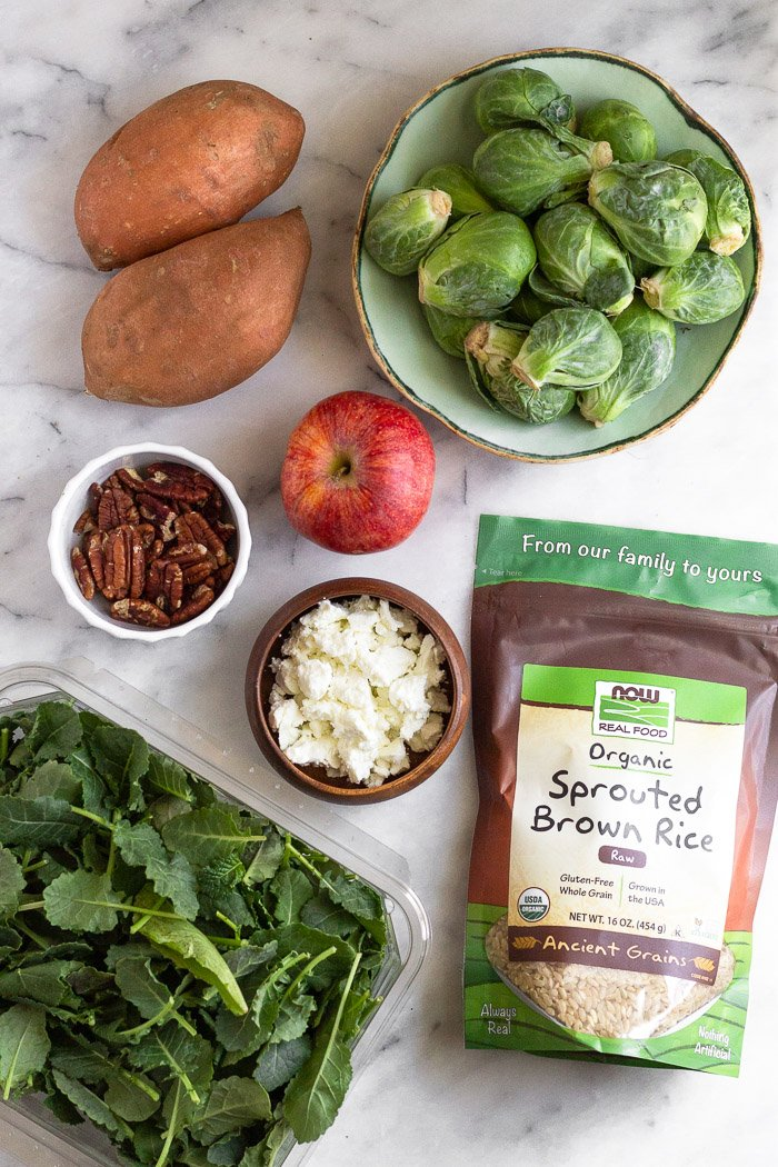 Overhead shot of a countertop with a bowl of Brussels, bag of brown rice, container of greens, bowl of goat cheese, an apple, bowl of nuts, and two sweet potatoes.