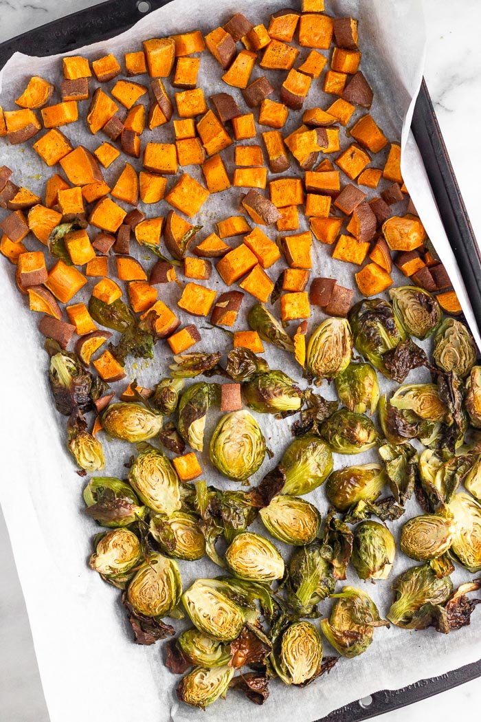 Overhead shot of roasted sweet potatoes and Brussel sprouts on a baking sheet.