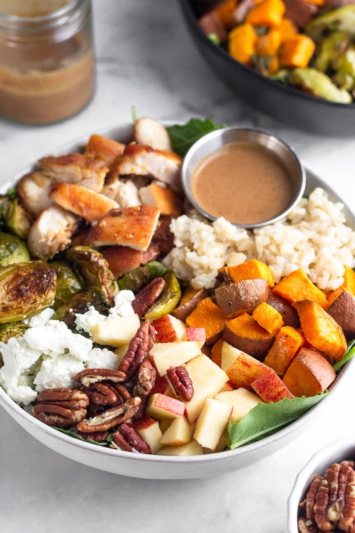 Homemade grain bowl with rice, sweet potatoes, apples, nuts, goat cheese, Brussel sprouts, chicken, and a creamy balsamic dressing.