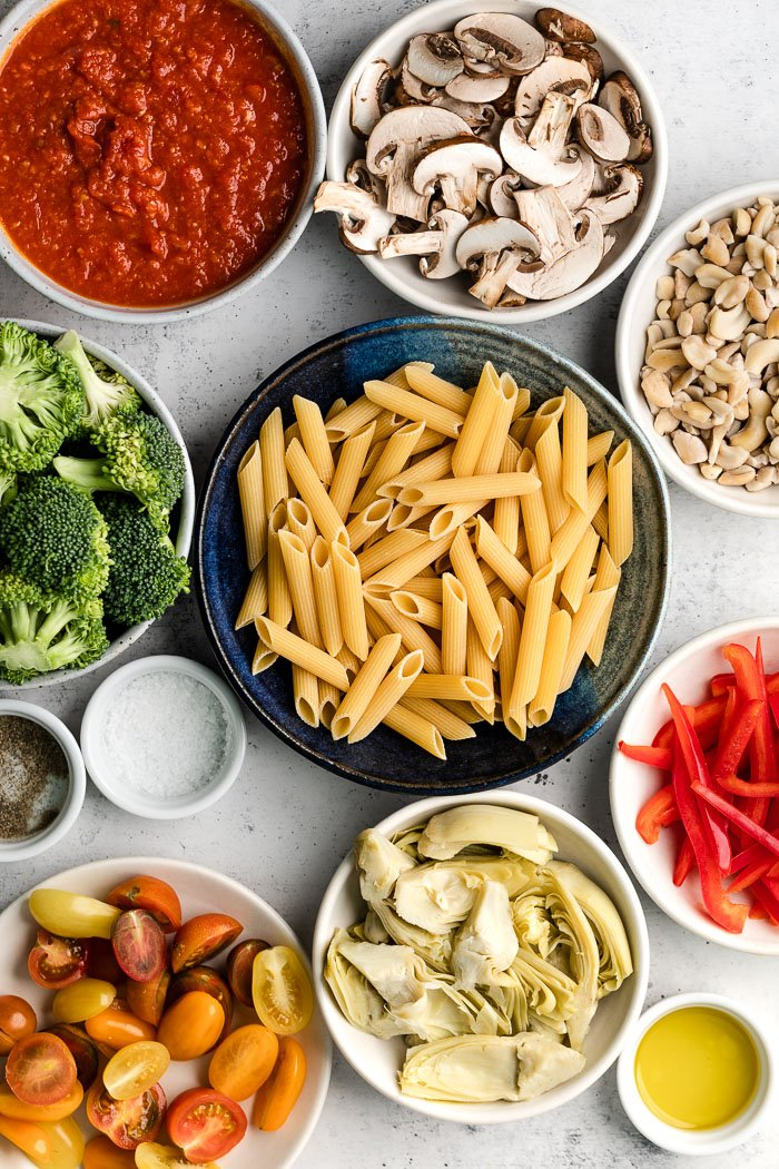 Overhead shot of a bunch of different bowls of pasta sauce, mushrooms, cashews, bell peppers, oil, artichokes, tomatoes, pasta, salt, pepper, and broccoli.