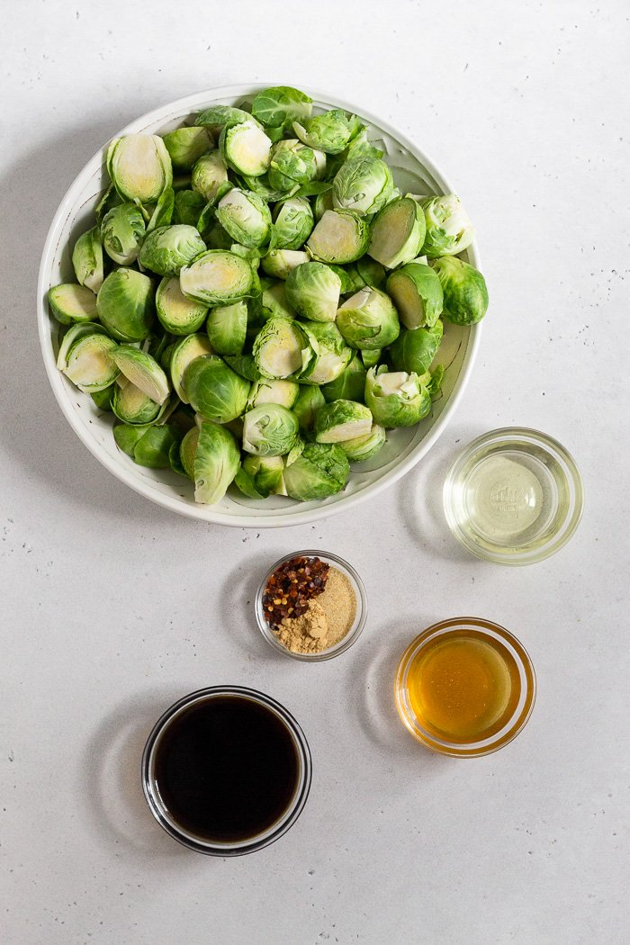 Overhead shot of a large bowl of halved brussel sprouts, small bowl of oil, small bowl of honey, small bowl of spices, and a small bowl of coconut aminos.