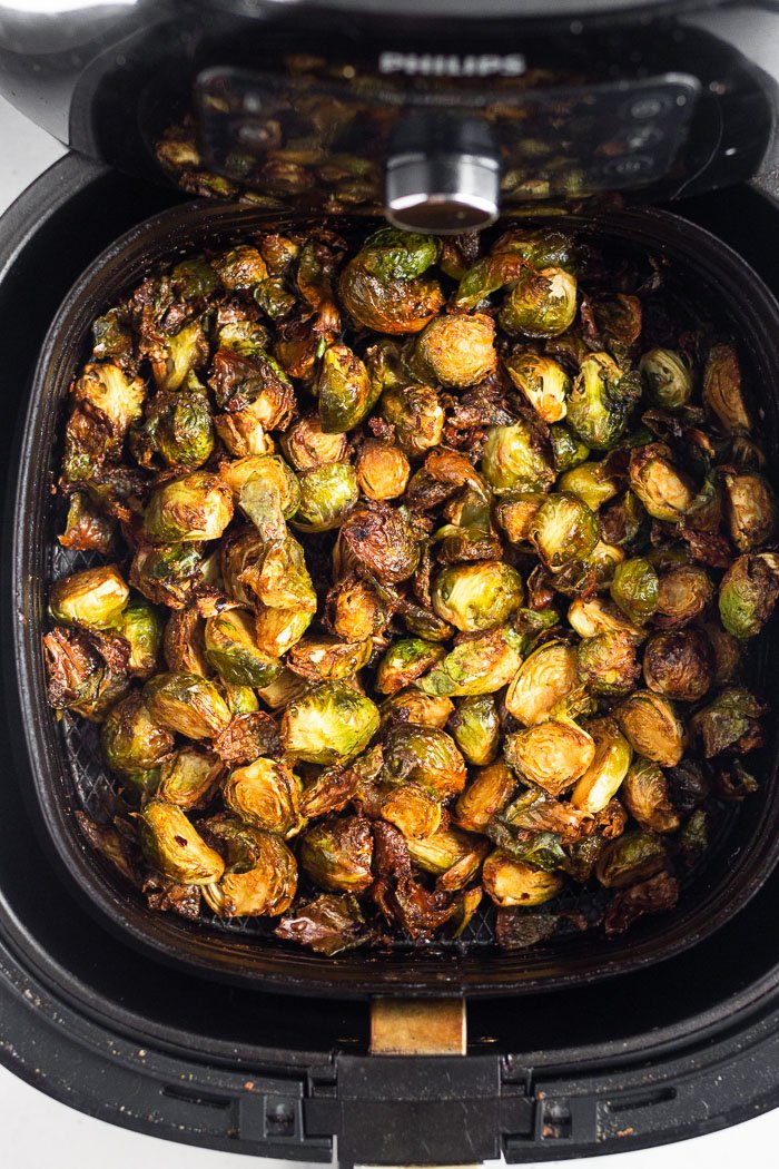 Overhead shot of crispy brussel sprouts in an air fryer basket.