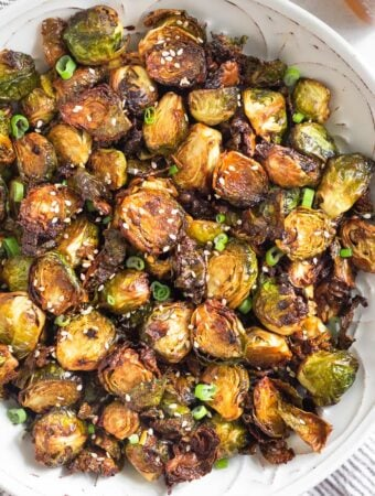 Overhead shot of crispy air fryer brussel sprouts in a large bowl topped with sesame seeds and green onions.