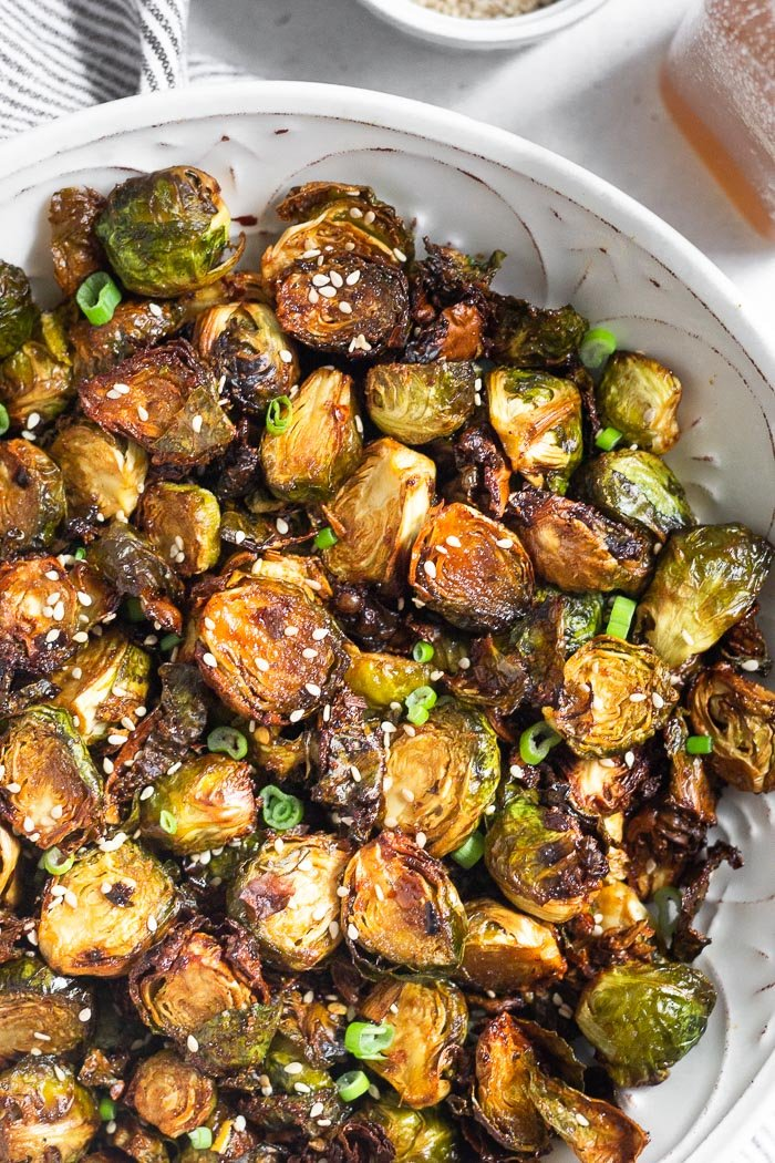 Close up of the best air fryer brussel sprouts in a large bowl. They are sprinkled with sesame seeds and green onions.
