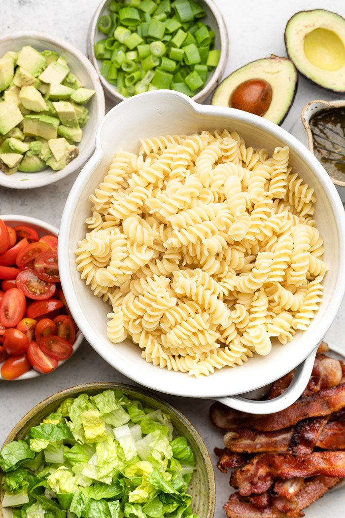 Overhead shot of a bowl of cooked pasta, plate of cooked bacon, bowl of chopped lettuce, bowl of cherry tomatoes, bowl of avocado, bowl of green onion, and some halved avocado and herbs.