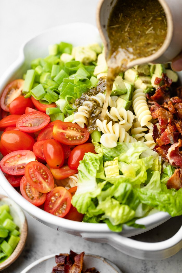 Bacon pasta salad in a large bowl with homemade pasta salad dressing being poured over top.