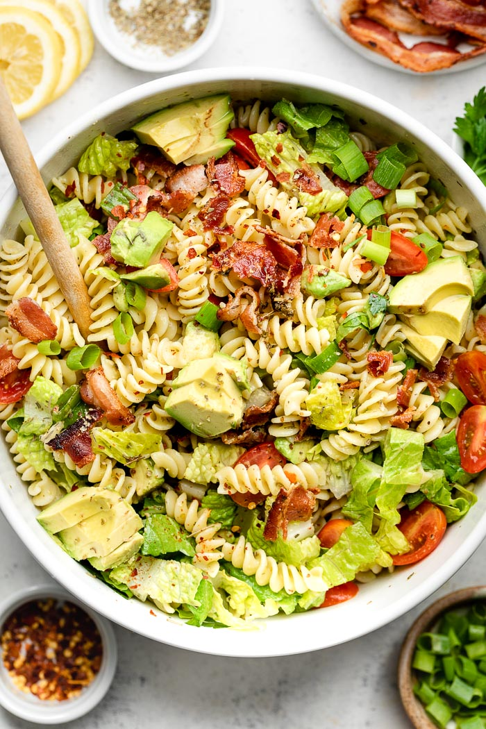 BLT pasta salad with Italian dressing and bacon in a large white bowl with a wooden spoon coming out of it. Around it is a few dishes of herbs, lemon, spices, and green onions.