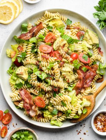 Blt pasta salad on a large white dish and a spoon in it. Around it is s