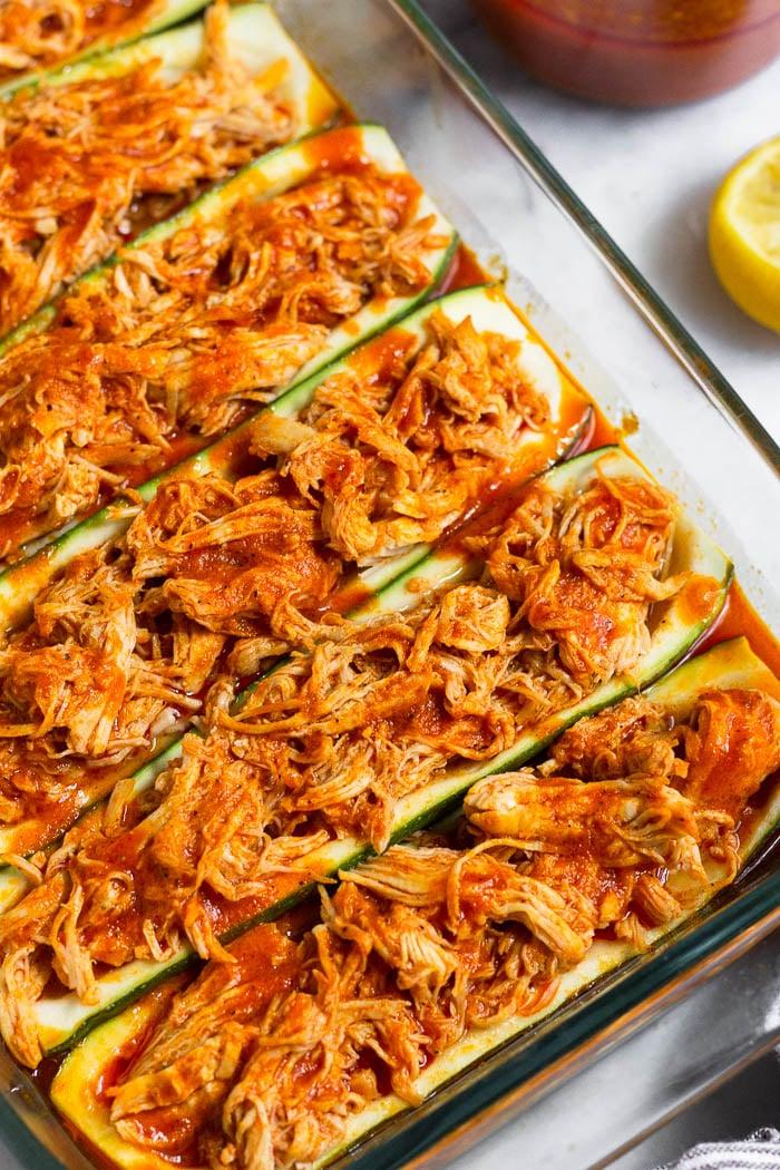 Zucchini boats recipe stuffed with buffalo chicken in a large glass pan.