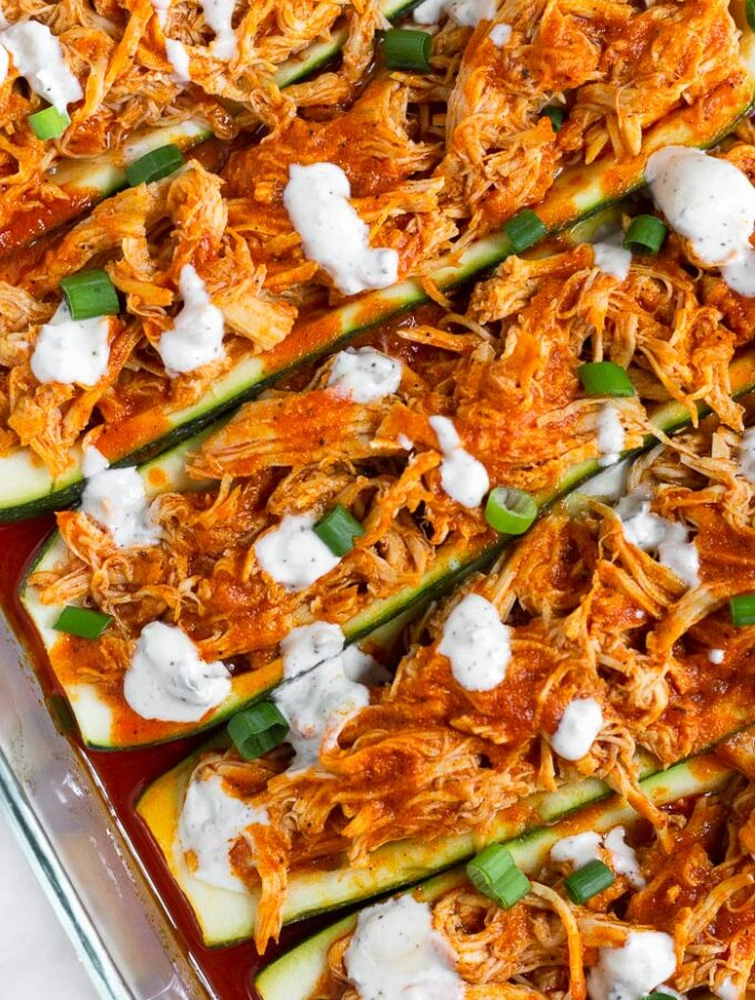 Close up of buffalo chicken zucchini boats topped with blue cheese dressing and green onions.