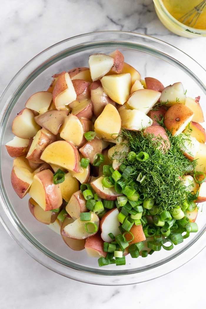 Overhead shot of a large glass bowl filled with cooked cubed red potatoes with honey mustard dressing, dill, and green onions over top.