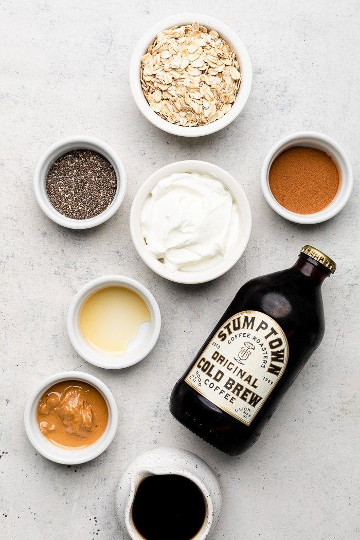 White counter top with small bowls filled with rolled oats, cinnamon, yogurt, chia seeds, honey, cashew butter, cold brew coffee, and a bottle of cold brew coffee.
