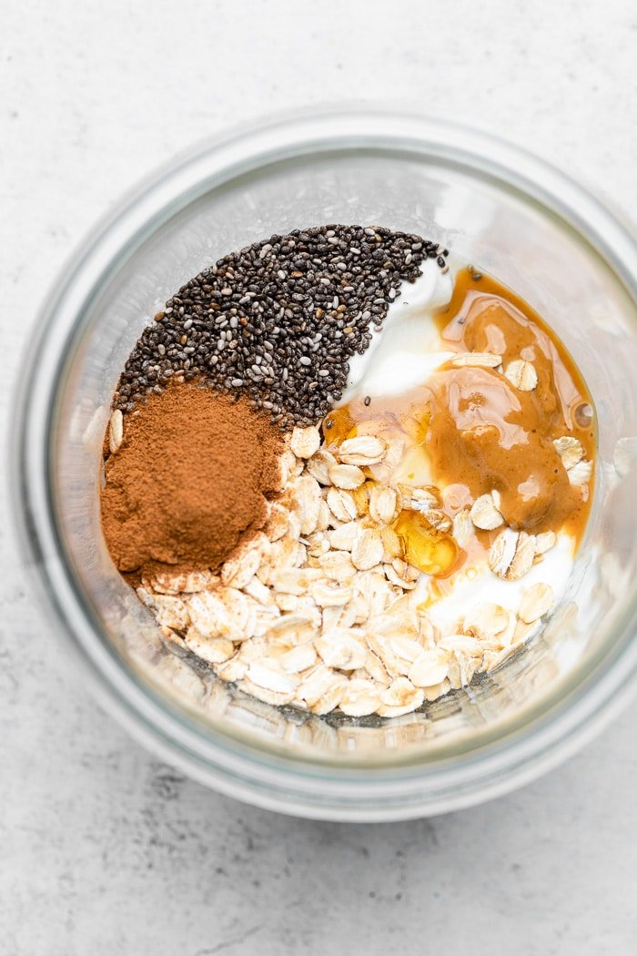 Overhead shot with rolled oats, cinnamon, chia seeds, yogurt, cashew butter, and honey in a large jar.