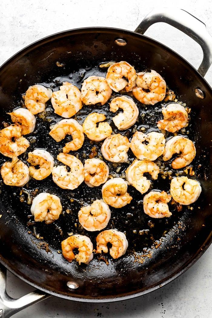 Sauté pan filled with cooked shrimp.