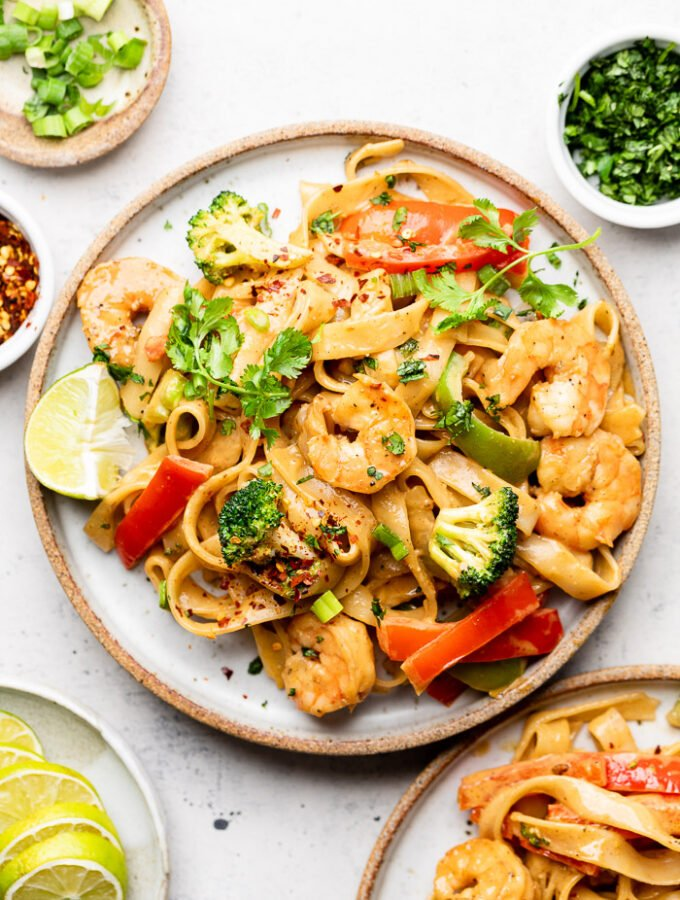 Plate of shrimp rice noodles with veggies and peanut sauce. It is topped with cilantro and has a lime wedge on the plate. Around it is another plate with shrimp noodles, small plate with lime wedges, bowl of red pepper flakes, bowl of chopped green onion, and a bowl of cilantro.